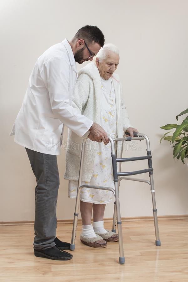 Balcones médicos de la rehabilitación La abuela aprende caminar con la ayuda de un caminante y ayudado por una enfermera imágenes de archivo libres de regalías