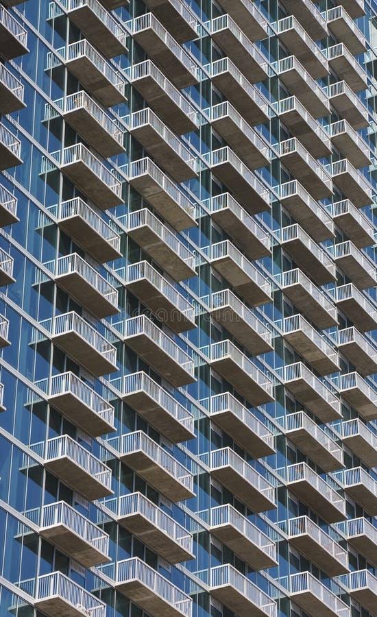 Balconi bianchi che aumentano sulla torretta di vetro blu del condominio fotografie stock libere da diritti