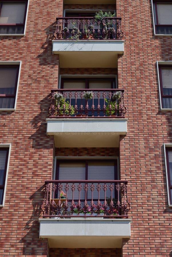 Balconi con i fiori di un condominio di multi-storia fotografie stock libere da diritti