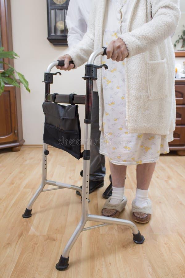 Balconi medici di riabilitazione La nonna impara camminare con l'aiuto di un camminatore ed assistito da un infermiere fotografia stock
