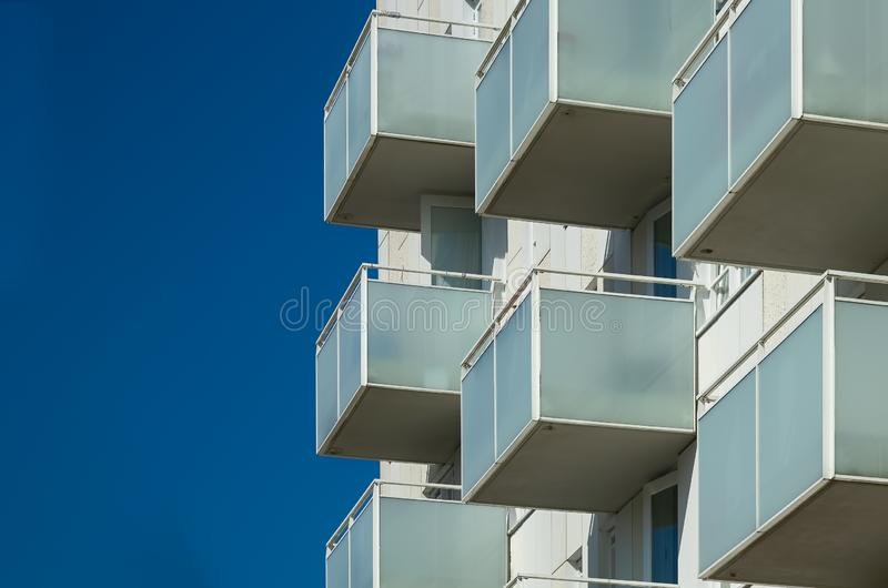 Balconies of an appartement building. Fragment of a facade of an appartement building with balconies agains a blue sky royalty free stock photos