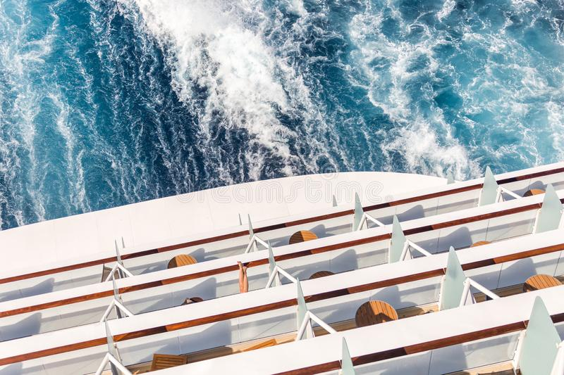 Balconies on a Cruise ship, decks with wake or trail. Balconies on a backof Cruise ship, decks with wake or trail on ocean surface royalty free stock image