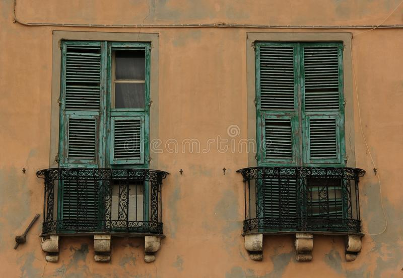 Balconies. With green window shutters opening up onto one of the narrow streets of Cagliari on the island of Sardinia, Italy stock photography