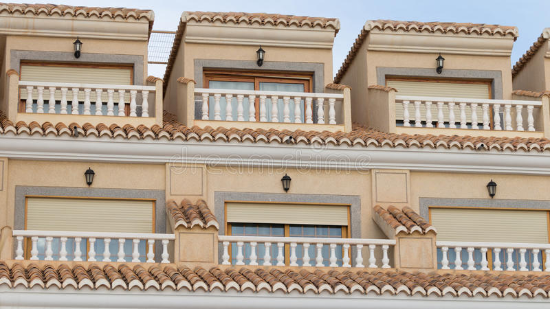 Balconies and roof areas. Small balconies with railings and balusters in the yellow apartment building and the tiles on the roof, in the seaside town stock images