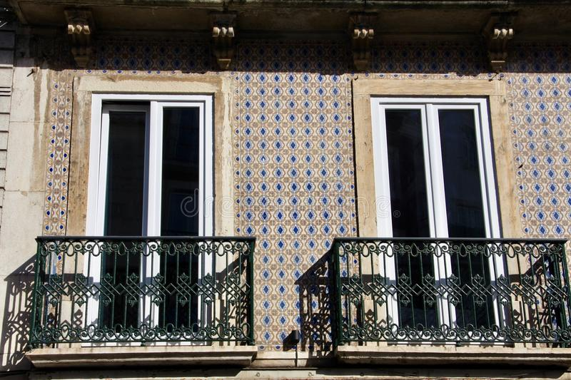 Two balconies on tiled by azulejo facade of building in Lisbon . Balconies on traditional portugal facade, two windows . Balconies with black wrought- iron royalty free stock images
