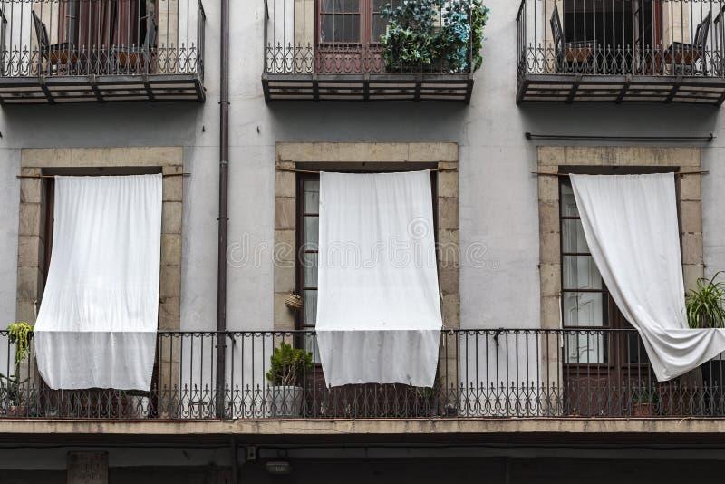 Balcons de détail de bâtiment de façade avec les rideaux blancs dans le quart soutenu par EL de Barcelone photos stock