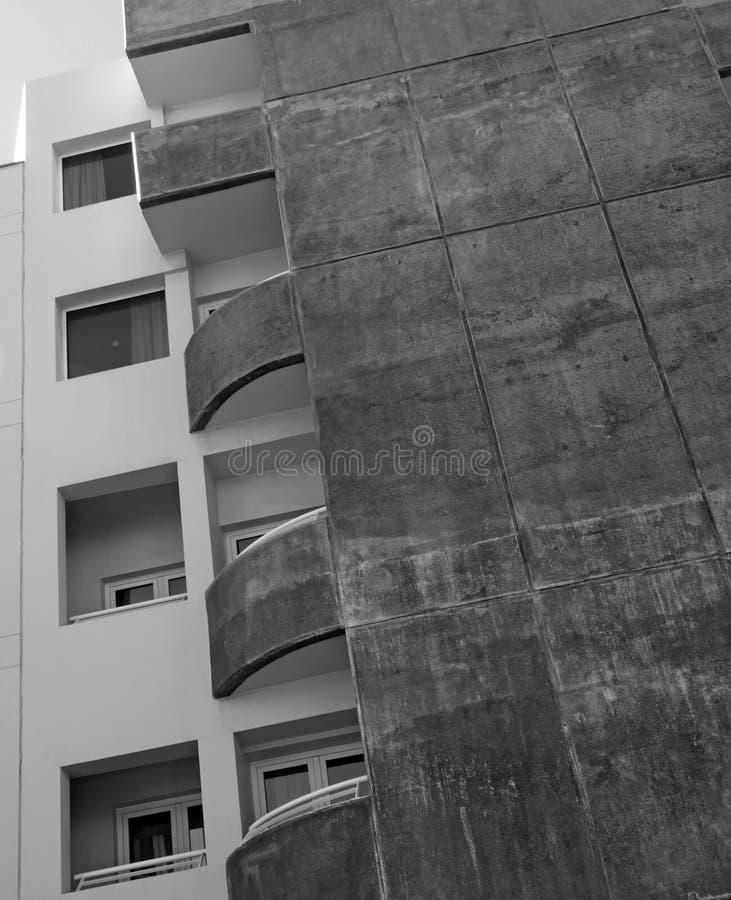 Balcons incurvés et fenêtres carrées dans un vieil immeuble en béton souillé photo stock