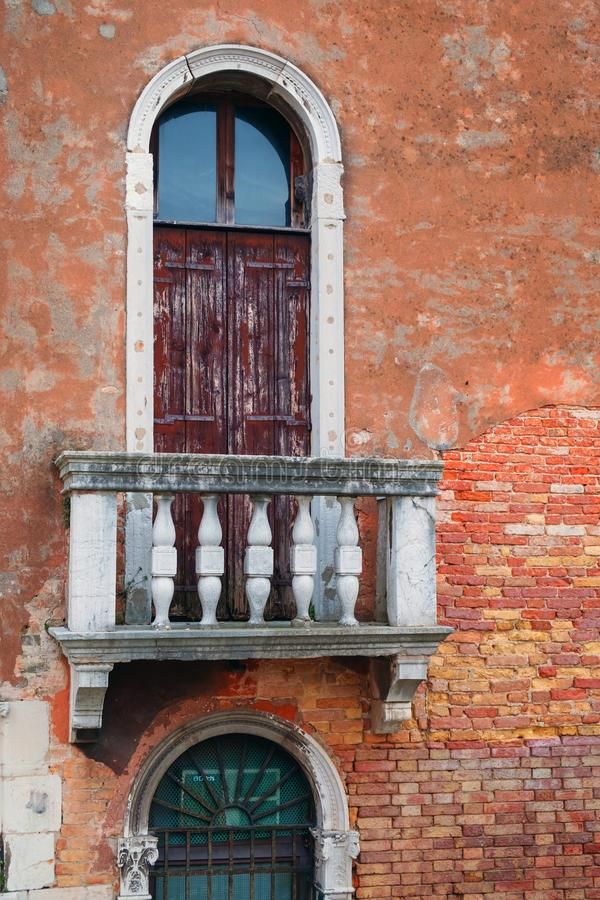 Balcony with closed wooden door. On brick wall facade stock photography