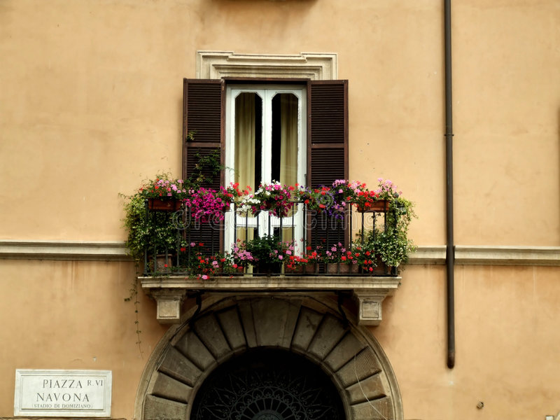 Balcony and a gate in Rome. Interesting colourful balcony in the Italian capital city - Rome stock photo