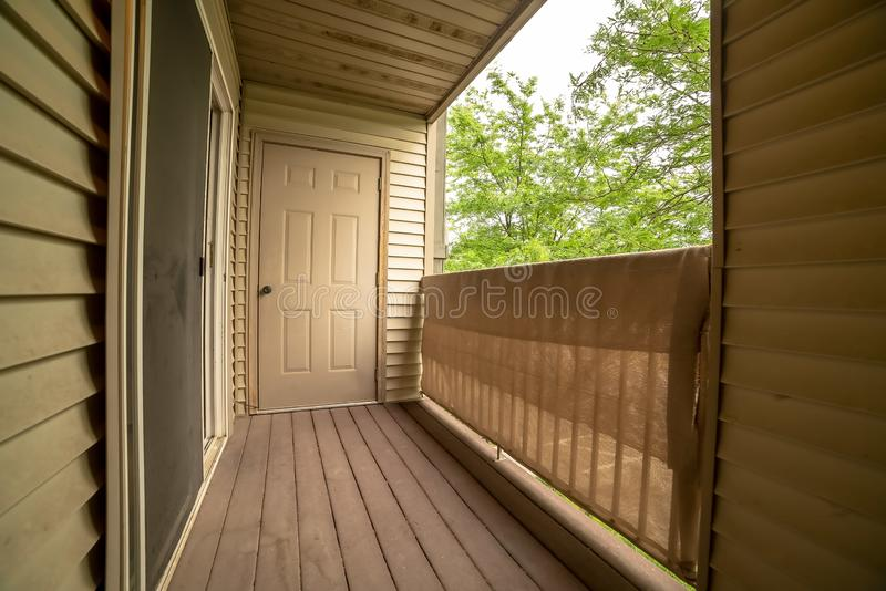 Balcony of a home with white wall siding and view of bomen against white sky stock foto