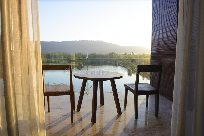 Balcony of house lake view with wooden table and chair.  royalty free stock image