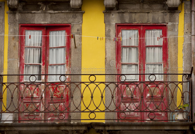 Balcony in Porto. Red doors contrast with yellow trim in a display of colour in Porto, a historical town in Portugal royalty free stock image