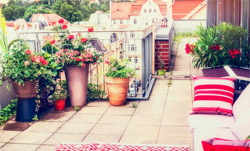 Balcony or terrace patio design with comfortable rattan furniture and patio flowers pots. Urban lifestyle, outdoor royalty free stock image