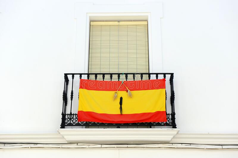 Balcony of a whitewashed house in a southern Spanish town with the flag of Spain with a black ribbon of mourning in memory of thos royalty free stock photos