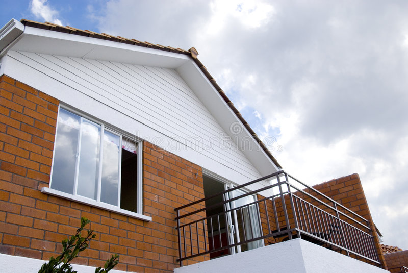 Balcony and window. Detail of a new two floor house with sky and clouds background royalty free stock photo