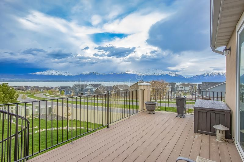 Balcony with wooden floor and metal railing overlooking lake and mountain. Houses along a curving road can also be seen under the striking cloudy blue sky royalty free stock photos