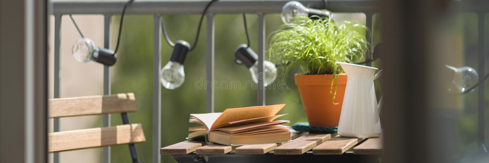 Cozy balcony with wooden table. Panorama of cozy balcony with small, wooden table and chair stock photography