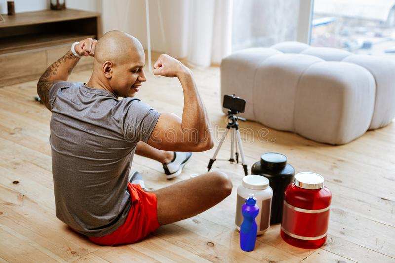 Bald bodybuilder making photo using smartphone and phone stand. Phone stand. Bald bodybuilder showing his biceps while making photo using smartphone and phone stock images