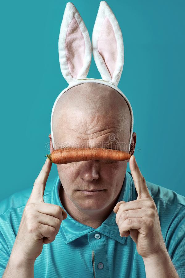 Bald brutal man in a light shirt and Bunny ears. In the hands of he holds a carrot, which closes eyes. Bald brutal man in a light t-shirt and Bunny ears. In the royalty free stock photography