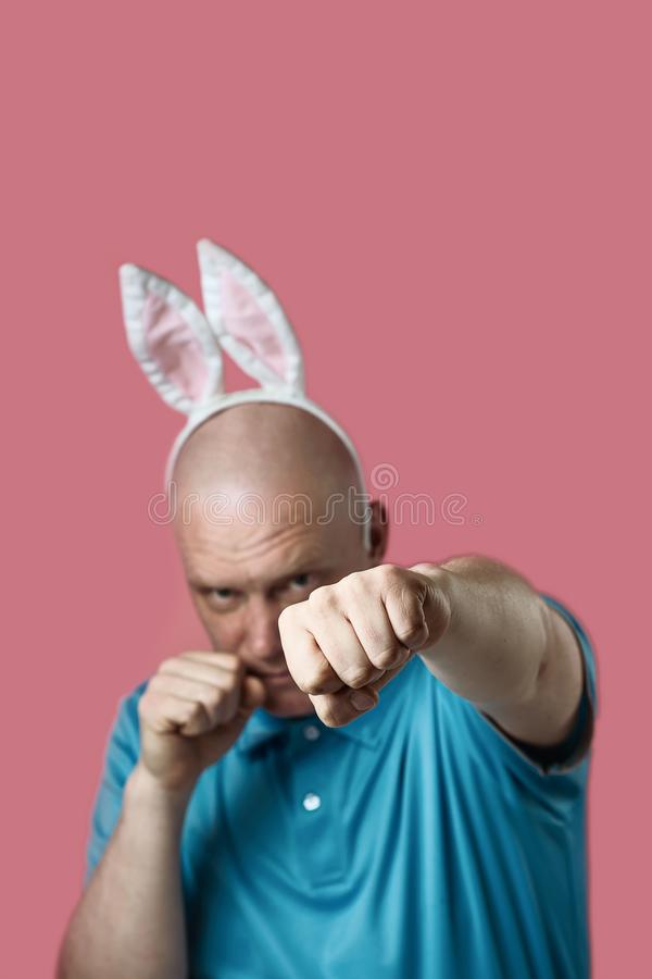 Bald brutal man in light t-shirt and Bunny ears. Hands he strikes as in Boxing. Bald brutal man in a light t-shirt and Bunny ears. Hands he strikes as in Boxing stock photography