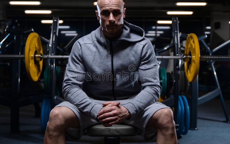 Brutal strong bodybuilder athletic men pumping up muscles with d. Bald brutal strong bodybuilder athletic fitness man pumping up abs muscles. Workout royalty free stock photography