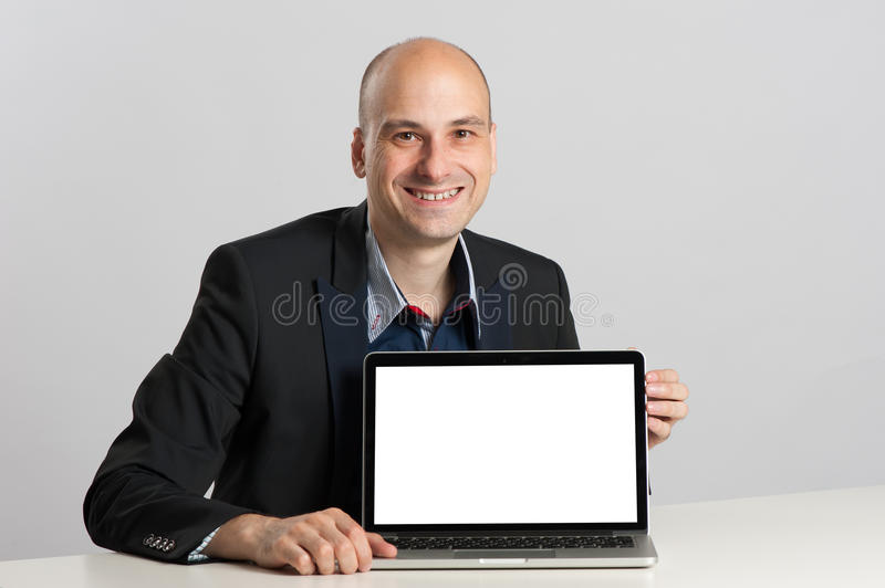 Bald businessman and laptop with copy space. Bald businessman sits at the desk showing laptop with copy space stock photo