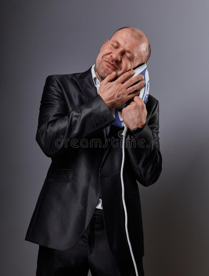 Bald happy comic business man holding the home comfort iron and caressing it with love and closed enjoying eyes in suit on grey royalty free stock photography