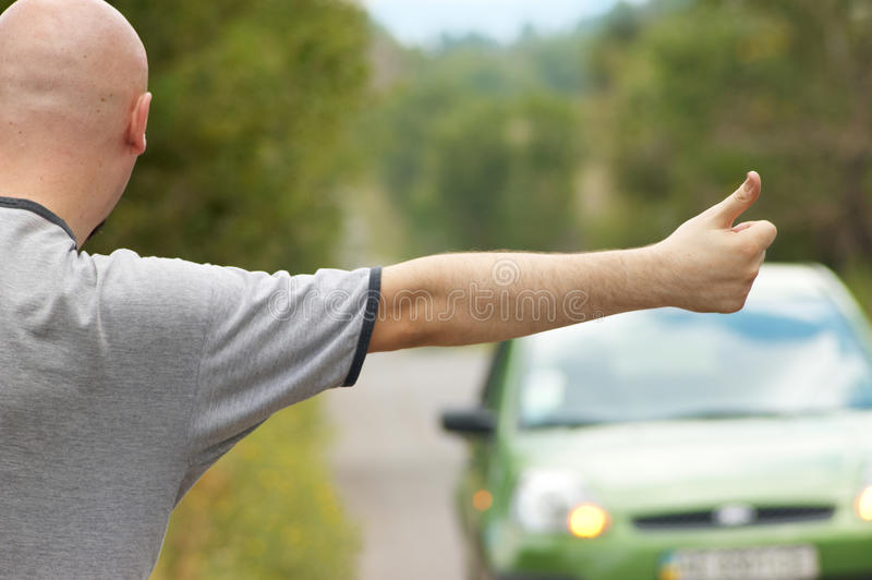 Bald-headed man hitching on road
