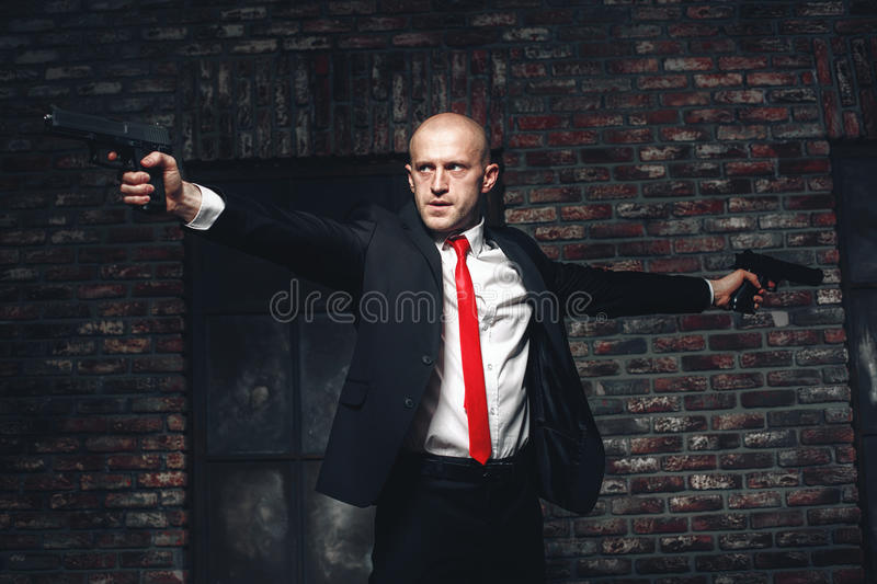 Bald hired killer in red tie aims a pistols. Serious hired assasin in red tie aims with two pistols. Professional secret agent concept. Murderer with guns royalty free stock photography