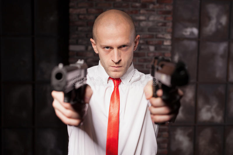 Bald hired killer in red tie aims a pistols. Serious hired assasin in red tie aims with two pistols. Professional secret agent concept. Murderer with guns stock photo
