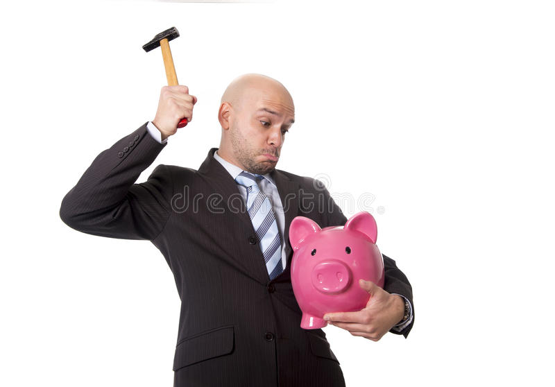 Bald Hispanic businessman with hammer in his hand holding pink piggybank ready to break the piggy bank and take money out. Bald Hispanic businessman with hammer stock images