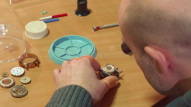 Clockmaker disassembles clock. Bald male clockmaker disassembling some mechanical clock. Close up of mature man unscrewing the from the clock mechanism royalty free stock photos