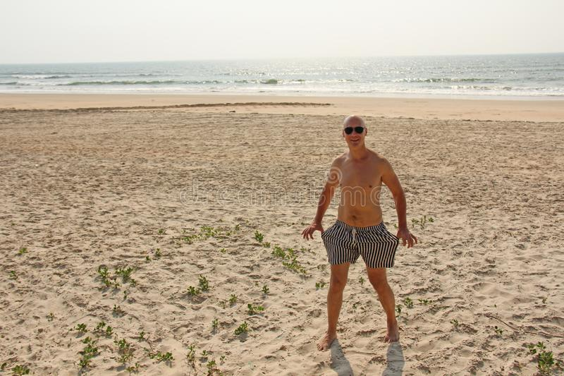 Bald man with a bare bare chest, in striped swimming trunks or s stock photo