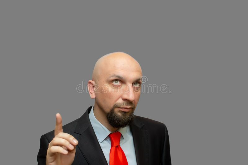 Bald man with beard looking and pointing finger up at grey background royalty free stock images