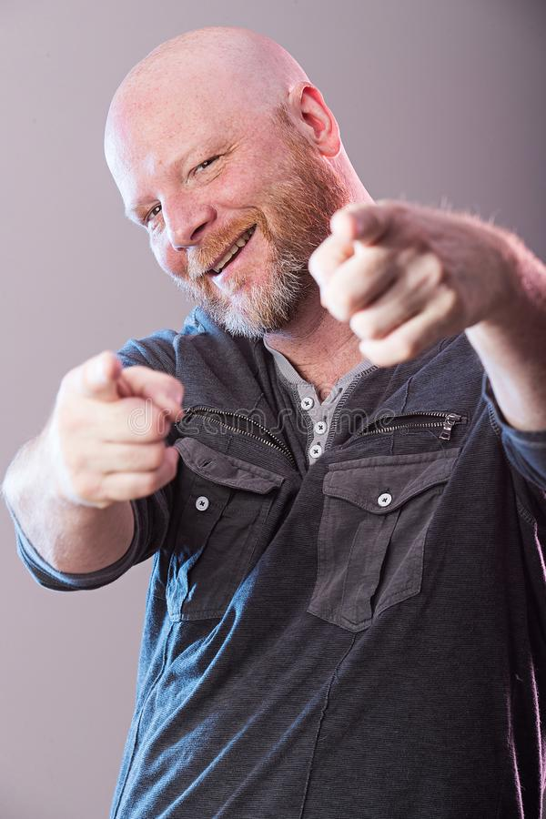 Bald man pointing and grinning royalty free stock photos