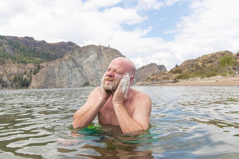 Man scrubbing face and beard with soap in a lake royalty free stock photography