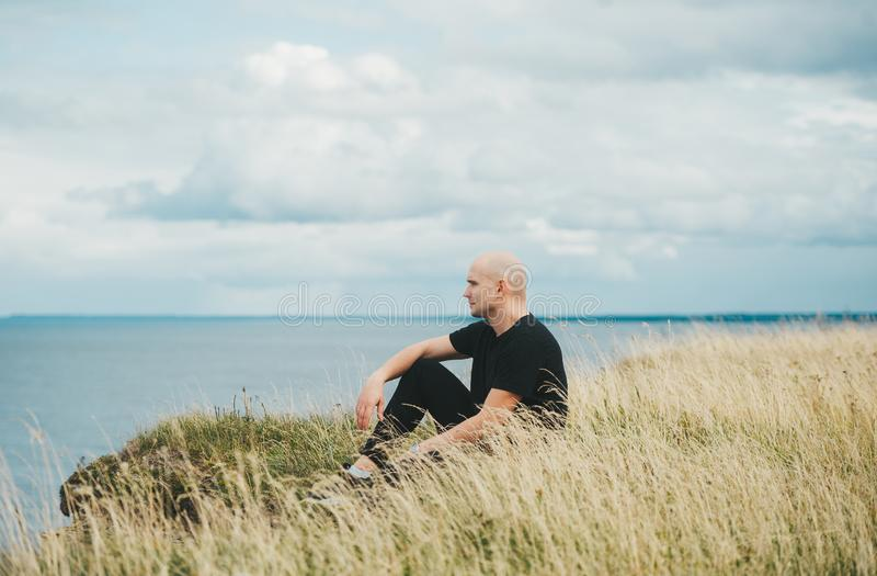 A bald man in black shirt sitting on grass on the edge of the rocky coast of the Baltic sea stock image