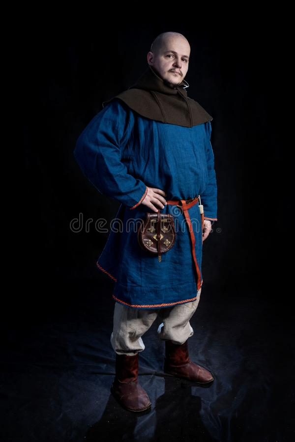 Bald man in casual clothes and hood of the viking age. On black background royalty free stock photos