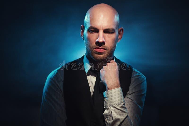 Bald man on a dark background. Dour bald man on a dark background royalty free stock photos