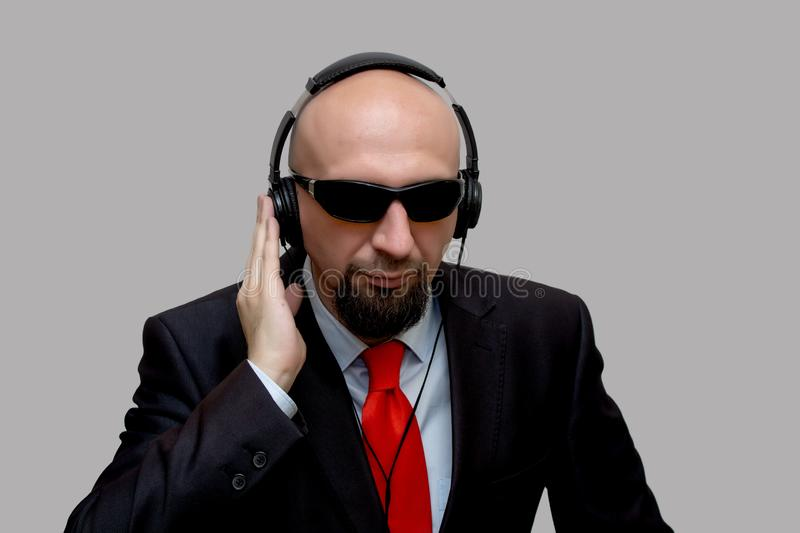 A bald man with headphones, listening to the secret conversation, the scout stock photos