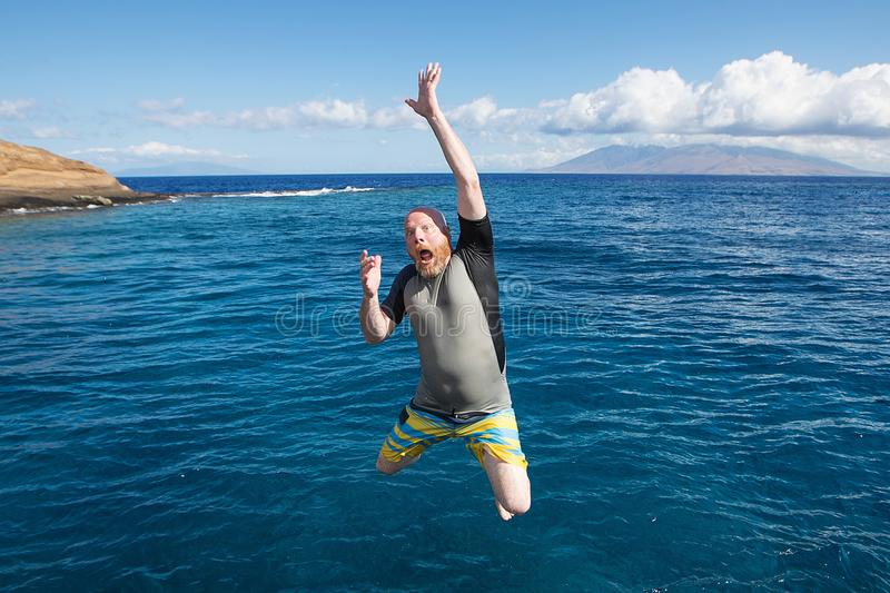 Bald man jumping into the ocean. Man jumping into the blue ocean stock photography
