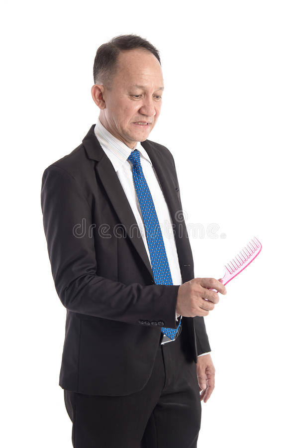 Bald man looking a comb in his hand on white background stock photography