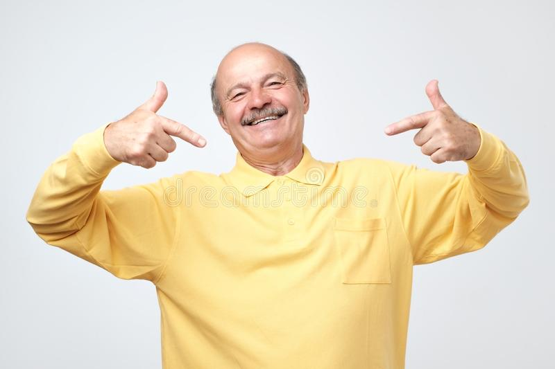Bald man looking confident with smile on face, pointing himself with fingers. Senior caucasian bald man looking confident with smile on face, pointing himself royalty free stock photo