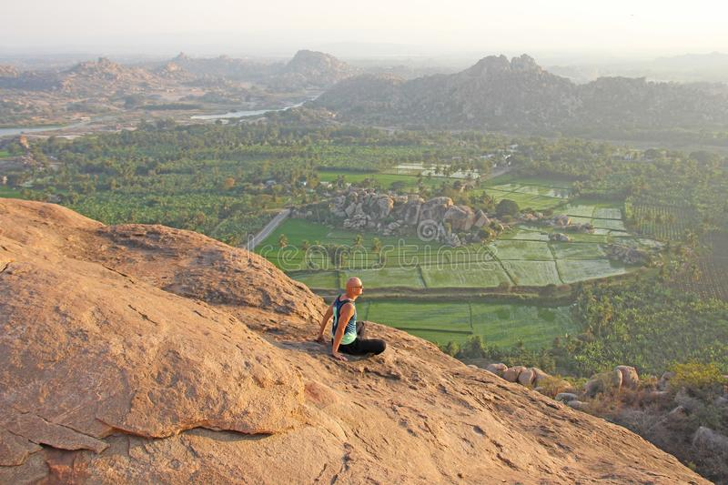 A bald man looks at the sunset at Hampi. Top Hampi. A man sits on top of a mountain and looks into the distance. Meditation, rest stock photo
