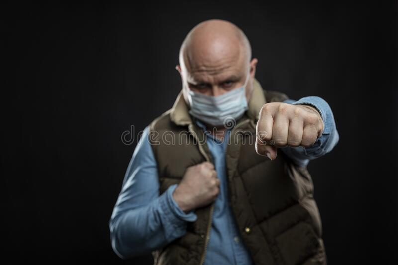 Bald man in a medical mask in a fighting stance. A blow to the disease. Self-isolation during the coronavirus pandemic. Black. Background royalty free stock photos