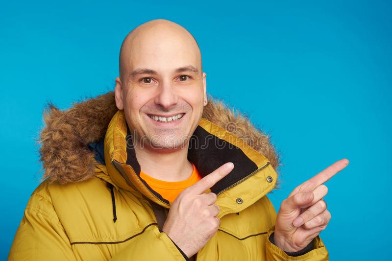 Bald man in winter coat pointing fingers royalty free stock images