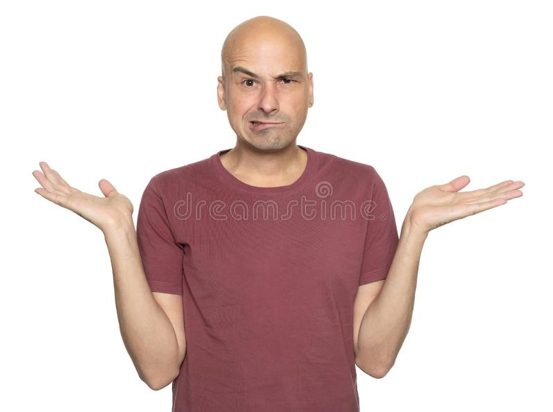 Bald man shrugging. Middle aged guy looking at camera with raised eyebrow. Isolated royalty free stock image
