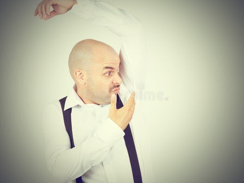 Bald man, smelling sniffing his armpit, something stinks bad royalty free stock photo