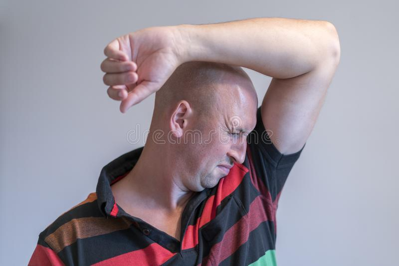 Bald man, smelling sniffing his armpit, something stinks bad. on grey background royalty free stock images