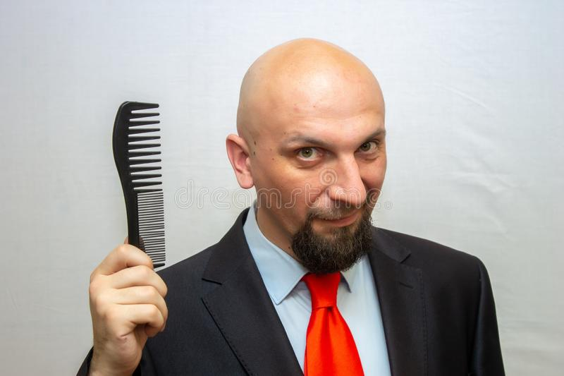 Bald man in a suit holding a smiling comb in his han stock photography